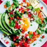 Mexican Hash Brown Stack. Crispy potato topped with sunny-side eggs, sliced avoc…